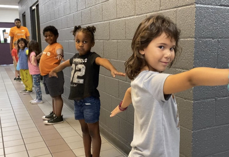 """caption: To help with social distancing, children at Valley of the Sun YMCA sites in Arizona were taught to make """"airplane arms"""" when standing in line."""