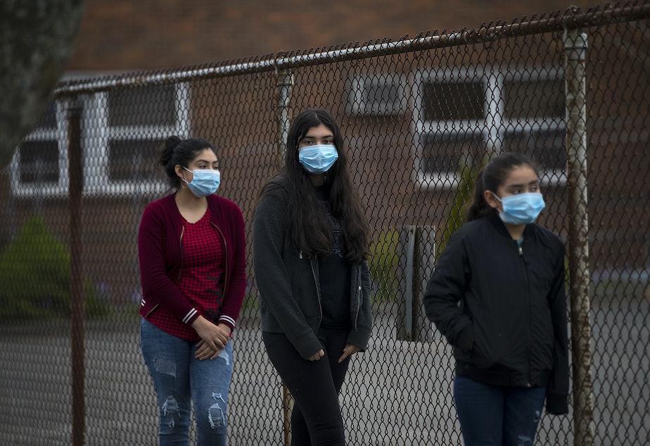 caption: From left, sisters Mia Hurtado, 14, Miliani Hurtado, 12, and Marleni Hurtado, 10, wait in line for walk and drive through confessions with Father Jose Alvarez on Friday, April 24, 2020, in the parking lot at Holy Family Roman Catholic Church in White Center.