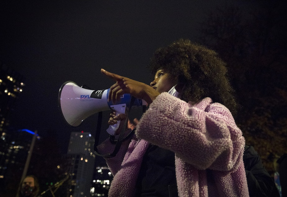 caption: Organizer Katie N. uses a megaphone while speaking to demonstrators on Monday, October 26, 2020, during the 150th day of protests for racial justice in Seattle.