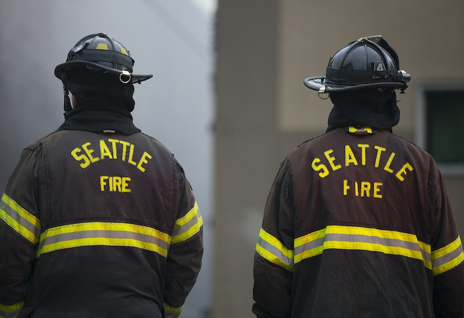 caption: Seattle firefighters work to put out a fire on Monday, October 7, 2019, at the intersection of NW Market Street and 24th Avenue Northwest in Seattle.