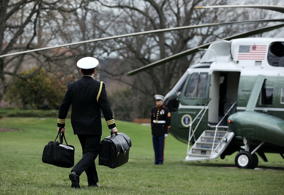 "caption: In March 2018, a White House military aide carries the ""football,"" a system that allows President Trump to launch a nuclear strike at any time."
