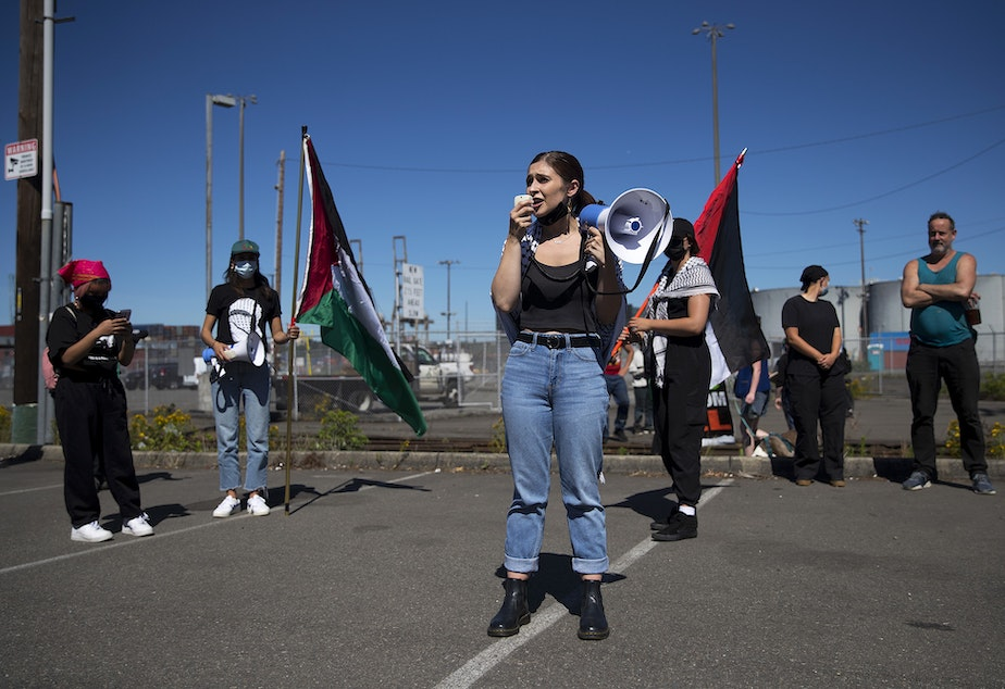 """caption: Aisha Mansour, a representative of Palestinian feminist organization Falastiniyat, leads a chant before blocking an intersection in protest of the Israeli Zim San Diego Vessel, on Thursday, June 17, 2021, at the Port of Seattle. """"By blocking Zim from unloading at our port, we have made clear that the city of Seattle does not welcome any business that profits from apartheid or human rights violations,"""" said Mansour."""