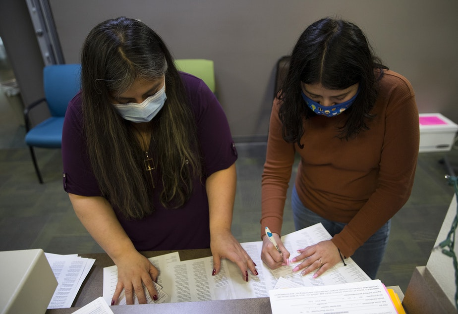 caption: Director of Island Drug, Fran Castro, left, and customer service representative Virginia Martinez, right, place the date as well as labels indicating the type of vaccination, lot number and expiration date on CDC vaccination record cards on Wednesday, April 7, 2021, at Island Drug in Oak Harbor.