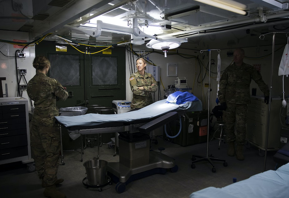 caption: U.S. Army soldiers are shown in the operating room of a military field hospital set up by soldiers from the 627th Army Hospital from Fort Carson, Colorado, as well as from Joint Base Lewis-McChord on Tuesday, March 31, 2020, at the CenturyLink Field Event Center in Seattle. The 250-bed hospital will be for non COVID-19 patients.