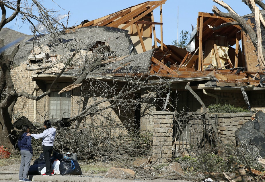 caption: Women stand outside a house damaged by a tornado in the Preston Hollow section of Dallas. The city was still cleaning up after the tornado on Monday.