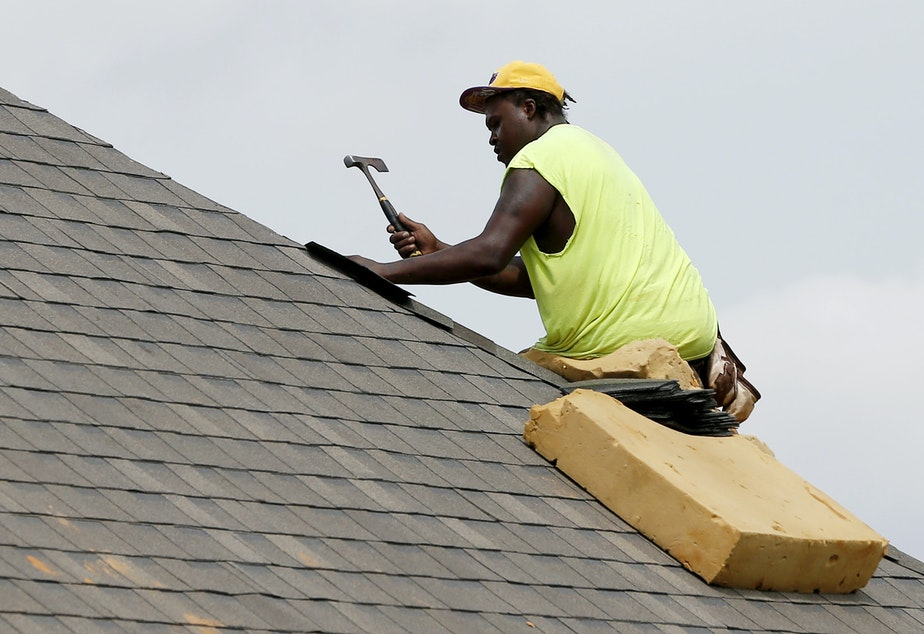 caption: A construction worker lays down shingles on the roof of a new house in Brandon, Miss., on June 19. Construction jobs rose 4,000 in July — below the 18,000 added in June and the 19,000 added in July 2018.
