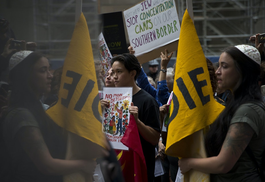 caption: Troy Osaki, 26, center, and Yaara Zaslow, right, listen to speakers as hundreds, including immigrants and members of the Jewish community, gathered on Thursday, August 8, 2019, to protest outside of Seattle's downtown ICE offices on 2nd Avenue.