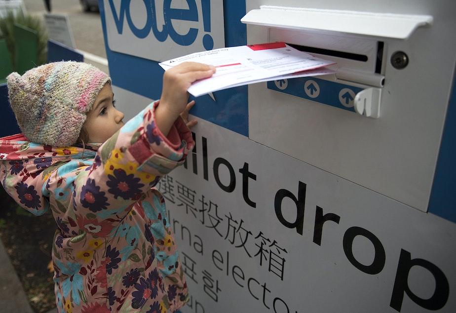 caption: FILE: Olivia Blanchard, 4, drops a ballot into the ballot drop box outside of the Seattle Public Library on Tuesday, November 7, 2017, in Ballard.