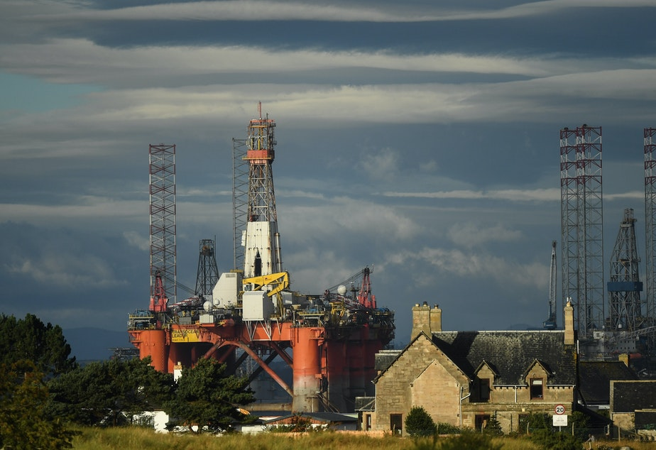 caption: An oil rig towers over houses in Nigg, Scotland, on September 8. Major players in the oil industry expect depressed oil demand and low prices to continue well into next year.