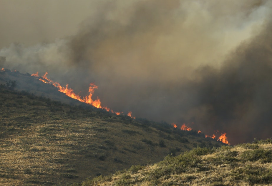 Flames and smoke rise on a hillside above Twisp River Road near Twisp, Wash., Wednesday, Aug. 19, 2015.