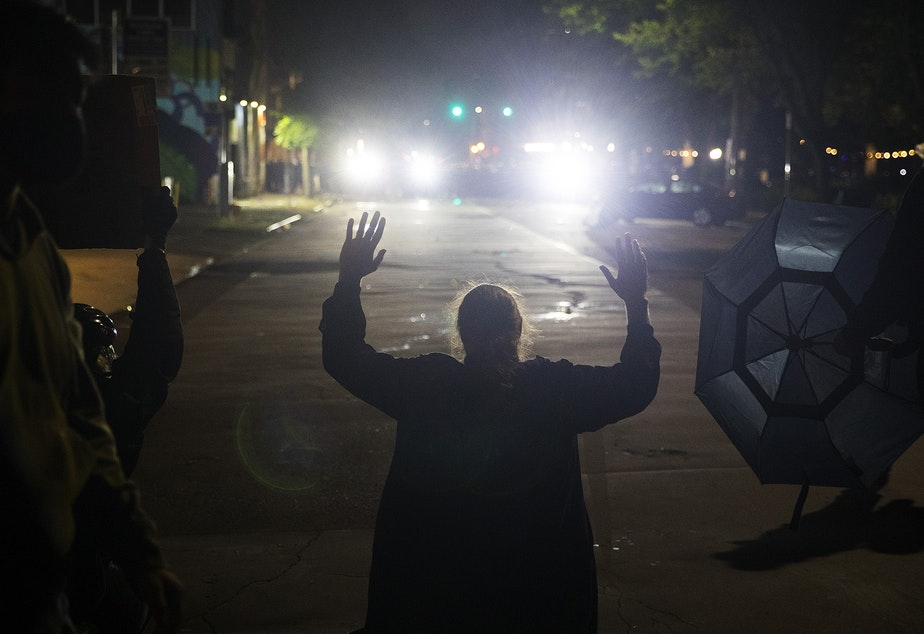 caption: A protester kneels with their hands in their air in front of hundreds of other protesters as Seattle police officers dressed in riot gear shine lights following the use tear gas, pepper spray, flash-bang grenades and rubber bullets on the fifth day of protests following the violent police killing of George Floyd on Tuesday, June 2, 2020, at the intersection 11th and Pine Streets in Seattle.