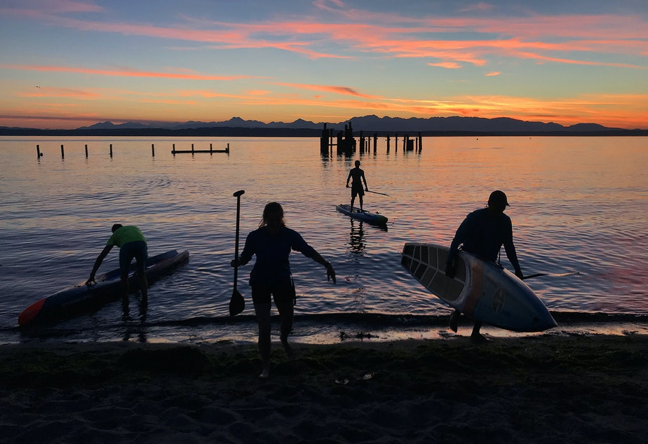 caption: A group of paddle boarders end their evening paddle on a small beach south of Golden Gardens on Monday, August 27, 2018, in Seattle.