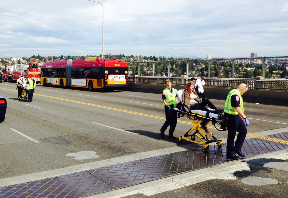 An injured person is taken from the scene of the Aurora Bridge bus crash on Thursday. Investigators have found the axle on the DUKW, or Duck, was faulty.