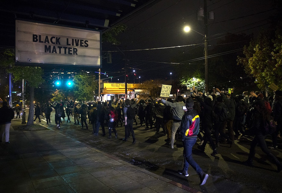caption: Demonstrators march from Cal Anderson Park to Westlake Park on Monday, October 26, 2020, during the 150th day of protests for racial justice in Seattle.