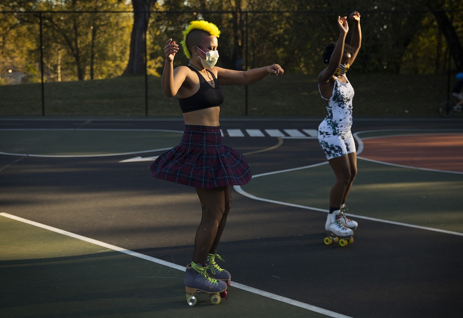 caption: Theo, left, and Tralonda Walker, right, skate during a decades themed skate meet up with Seattle Skates on Tuesday, October 6, 2020, at the White Center Bicycle Playground in Seattle.