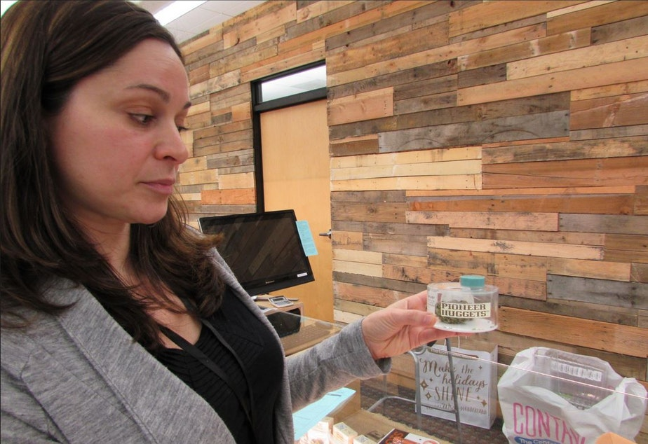 caption: Maria Moses of Dockside Cannabis in Shoreline, Washington, shows off a jar where customers can smell a marijuana sample.