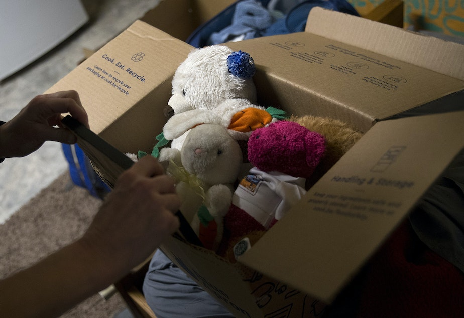 Jerri Clark packs a box full of stuffed animals, including a rabbit that her son Calvin kept with him while he was experiencing homelessness, on Friday, March 22, 2019, at his apartment in Seattle.