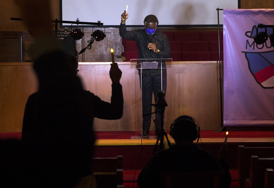 caption: Reverend Carey Anderson holds a candle in the air while leading a 'Mourning into Unity' prayer vigil in response to the coronavirus pandemic on Monday, October 19, 2020, at Seattle's First A-M-E Church on Capitol Hill.