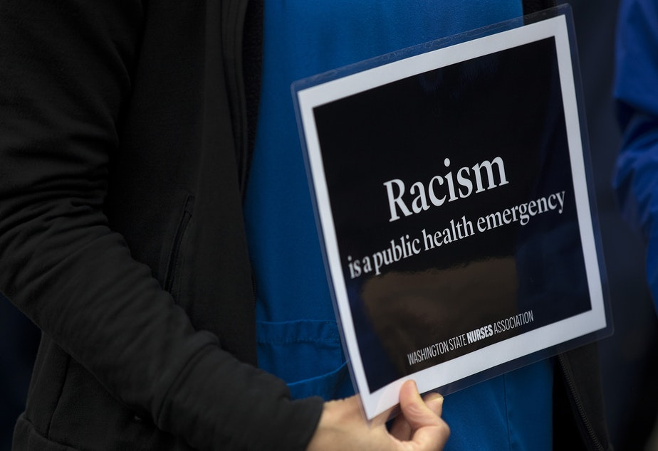 caption: Healthcare workers gather outside of Harborview Medical Center before marching to Seattle City Hall in protest to demand justice and an end to police violence on Saturday, June 6, 2020, in Seattle.