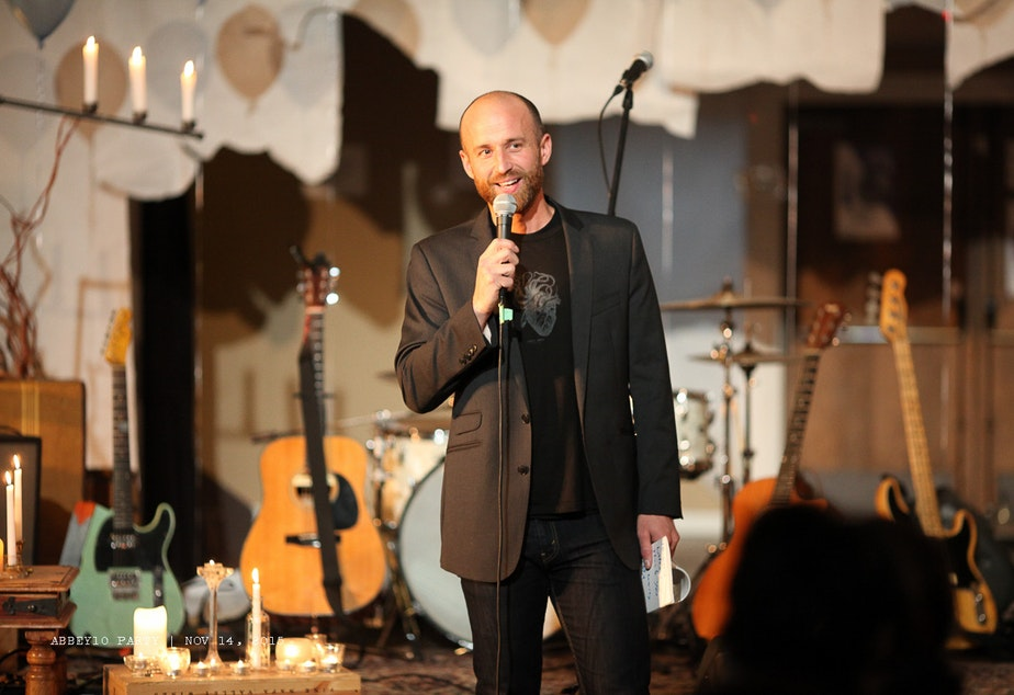 caption: Nathan Marion stands on stage at the Fremont Abbey during a community concert.