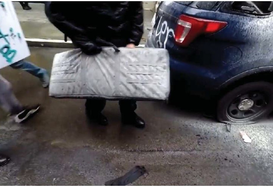 caption: Federal charging documents allege that this frame from a Youtube video depicts the theft of an SPD rifle in downtown Seattle on May 30, 2020.