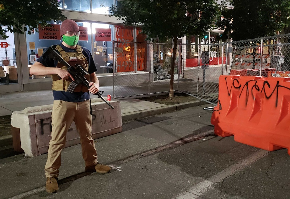 caption: A guard carrying an AR-15 rifle stands at the entrance to the CHAZ at 12th and Pike Street.