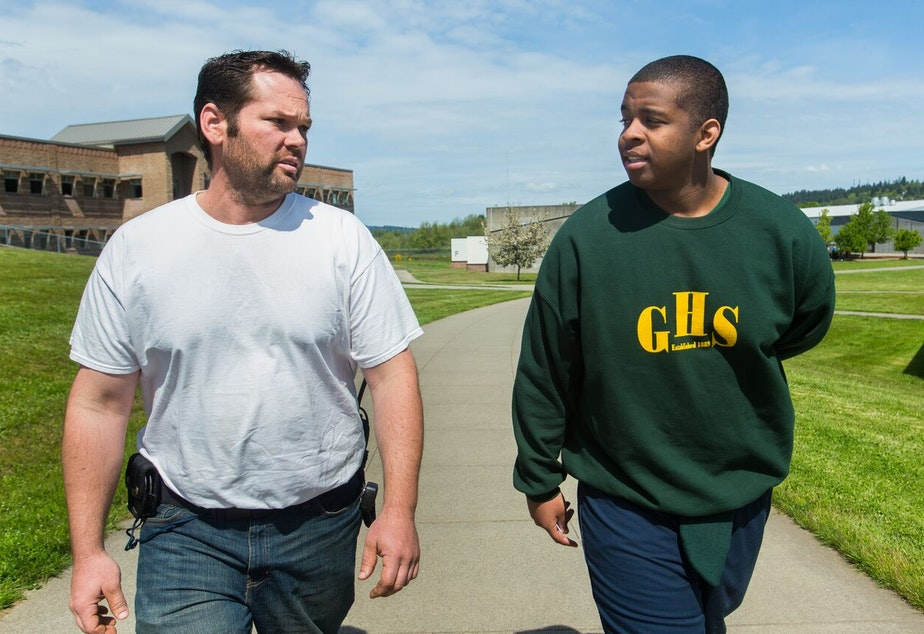 caption: Diontae Moore-Lyons, 17, right, is escorted back to his unit by manager Shawn Northcutt at Green Hill School in Chehalis, Wash., on Wednesday, May 10, 2017. Green Hill School is a medium/maximum security, fenced facility for teenage male offenders.