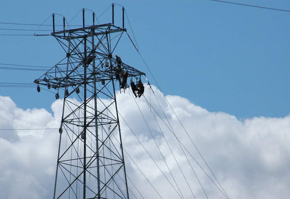 caption: Seattle City Light lineworkers on a transmission line 180 feet above the Seattle Ship Canal in 2011.