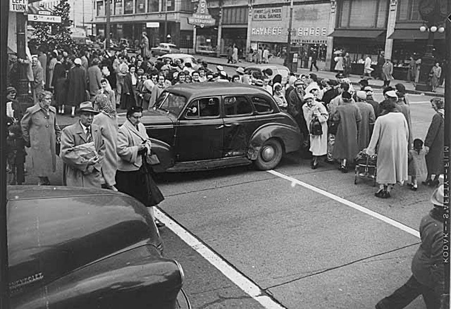 caption: Shoppers cross Fifth Avenue in Seattle during the Christmas season, 1954.
