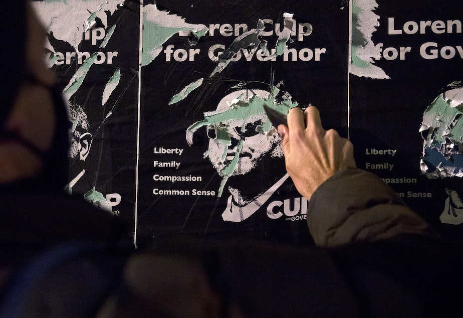 caption: A protester scratches the face of Loren Culp on a set of flyers with a knife as hundreds marched through the Pioneer Square neighborhood during a march focusing on counting every vote and protecting every person on Wednesday, November 4, 2020, in Seattle.