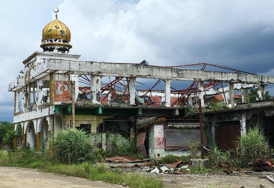 caption: The skeletal remains of a mosque stand amid overgrown shrubs. Authorities say 25 mosques were destroyed in the district most affected by the five months of fighting between government forces and ISIS militants in Marawi.
