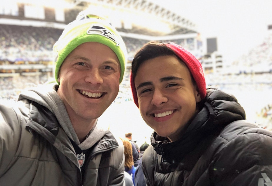 caption: Eriberto Saavedra Felix (right) and his teacher and mentor, Reid Sunblad, attend a Seahawks game — even though Eriberto is a 49ers fan.