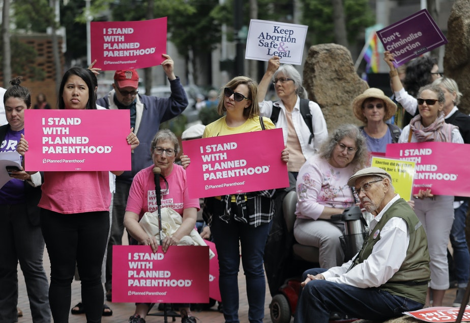 caption: FILE - In this July 10, 2018 file photo, protesters hold signs supporting Planned Parenthood in Seattle, as they demonstrate against President Donald Trump and his choice of federal appeals Judge Brett Kavanaugh as his second nominee to the Supreme Court.