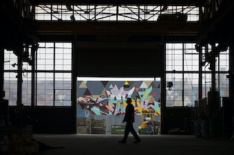 An Alaskan Copper Works employee walks in the  warehouse on Friday, September 8, 2017, in front of a mural painted by artists Blaine Fontana, Sneke, Hews and APaul, along the Sodo Track, in Seattle.