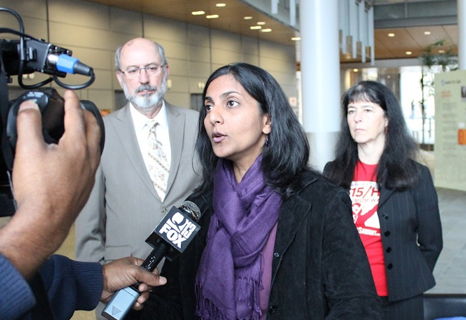 caption: City Council candidate Kshama Sawant, a member of the Socialist Alternative Party, with Democratic Party supporters Daniel Norton and Jeanne Legault.