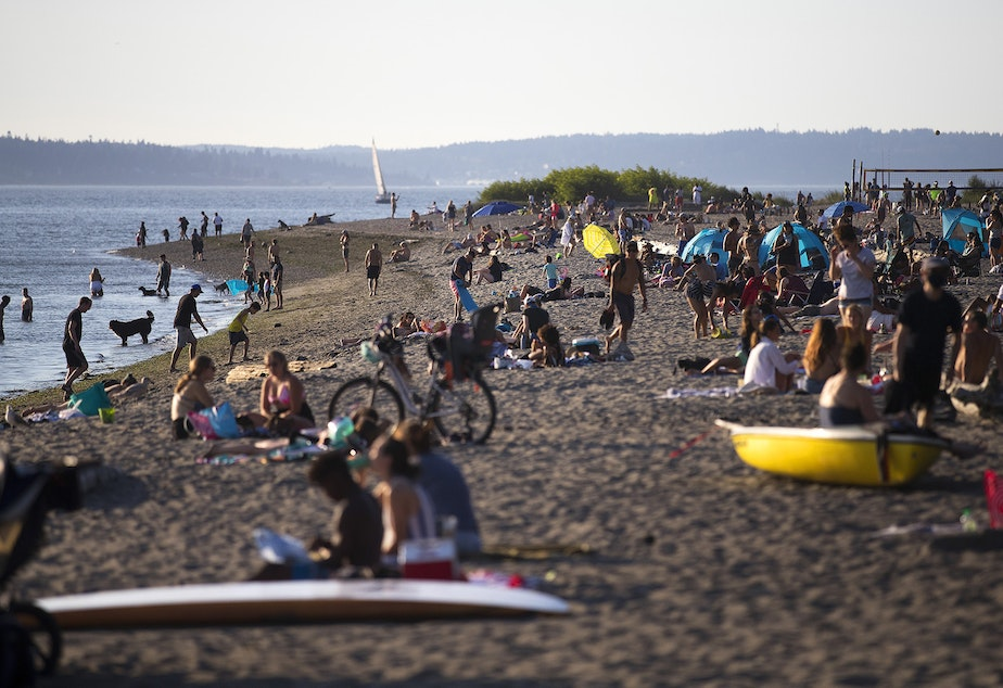 caption: Crowds gather on Wednesday, July 29, 2020, at Golden Gardens Park in Seattle as cases of Covid-19, along with related deaths, continue to dramatically rise in the region.