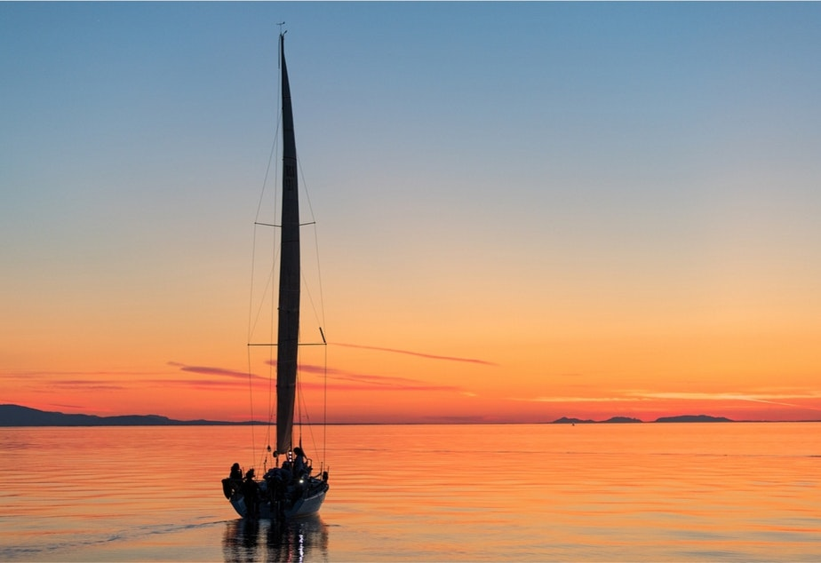 caption: Sail Like a Girl heads off into the sunset.