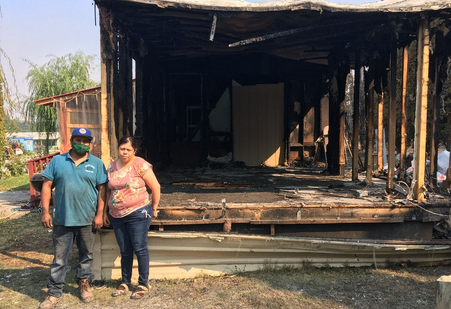caption: Ignacio and Araceli Gildo stand outside the burned remains of their home in Bridgeport, WA.