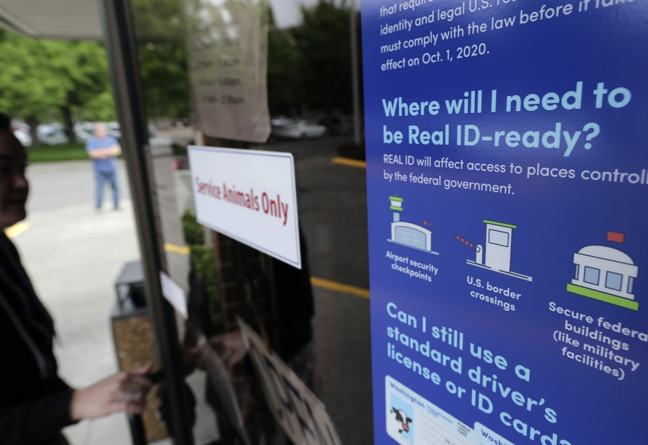A customer opens the door of a Washington state Dept. of Licensing office in Lacey, Wash.