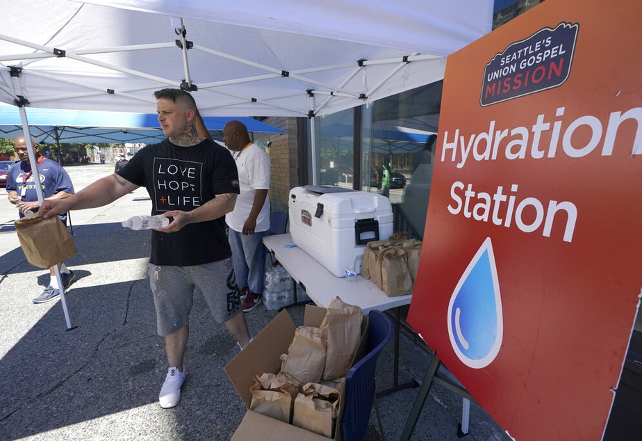caption: Carlos Ramos hands out bottles of water and sack lunches, Monday, June 28, 2021, as he works at a hydration station in front of the Union Gospel Mission in Seattle. Seattle and other cities broke all-time heat records over the weekend, with temperatures soaring well above 100 degrees Fahrenheit (37.8 Celsius).