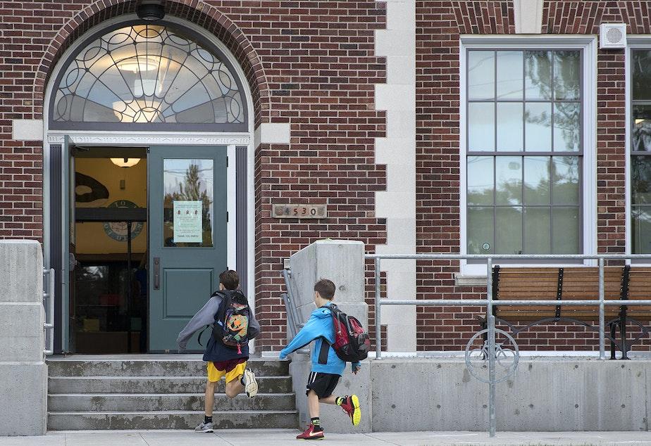 caption: Two boys run towards Laurelhurst Elementary School on Friday, June 16, 2017, on NE 47th St., in Seattle, Washington.
