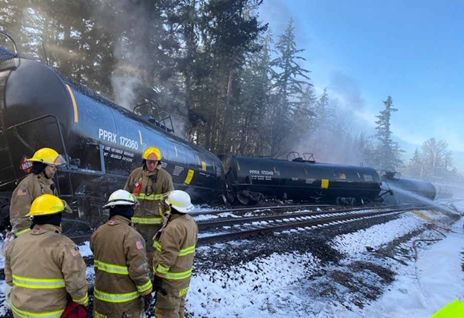 caption: Fire crews respond to the scene of a derailed train in the city of Custer, WA in Whatcom County on Tuesday, December 22, 2020. A BNSF spokesperson said seven train cars derailed and two caught fire.