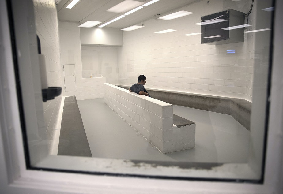 caption: A detainee sits in the intake area at the Tacoma Detention Center in 2017.