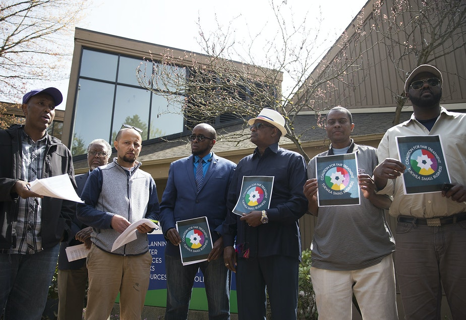 From left, Abdi Adan and Tawfik Maudah and other supporters/business owners read over the  demands that they will make before entering Tukwila City Hall with community members and business owners on Thursday, April 19, 2018, in Tukwila.