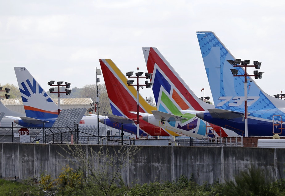 caption: A line of Boeing 737 MAX jets sit parked on the airfield adjacent to a Boeing production plant last month in Renton, Wash. Boeing now says it is cutting thousands of jobs.