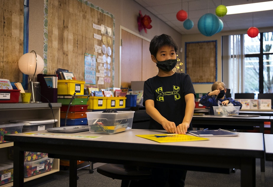 caption: Anthony, a second-grade student at Somerset Elementary School, opens school supplies and folders from his cubby on Thursday, January 21, 2021, as second-grade students returned to in-person learning in Bellevue.