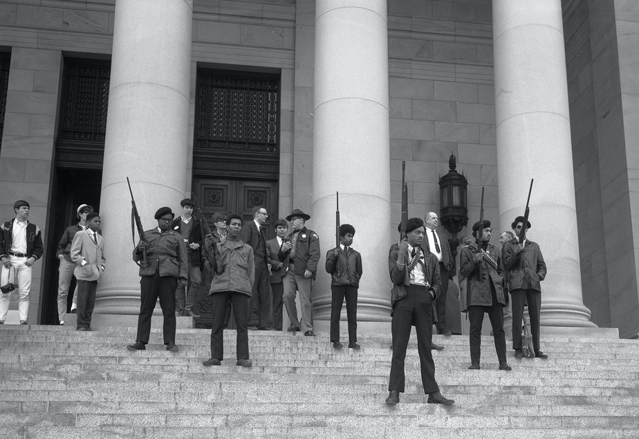 caption: Elmer Dixon and other Seattle Black Panthers gather on the steps of the Capitol in Olympia on February 28, 1969, to protest a bill aiming to it a crime to exhibit firearms with 'an intent to intimidate others.'