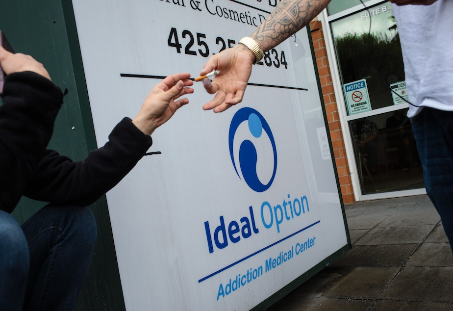 Patients share a cigarette outside the Everett Ideal Option clinic, an addiction treatment center. (Finding Fixes)