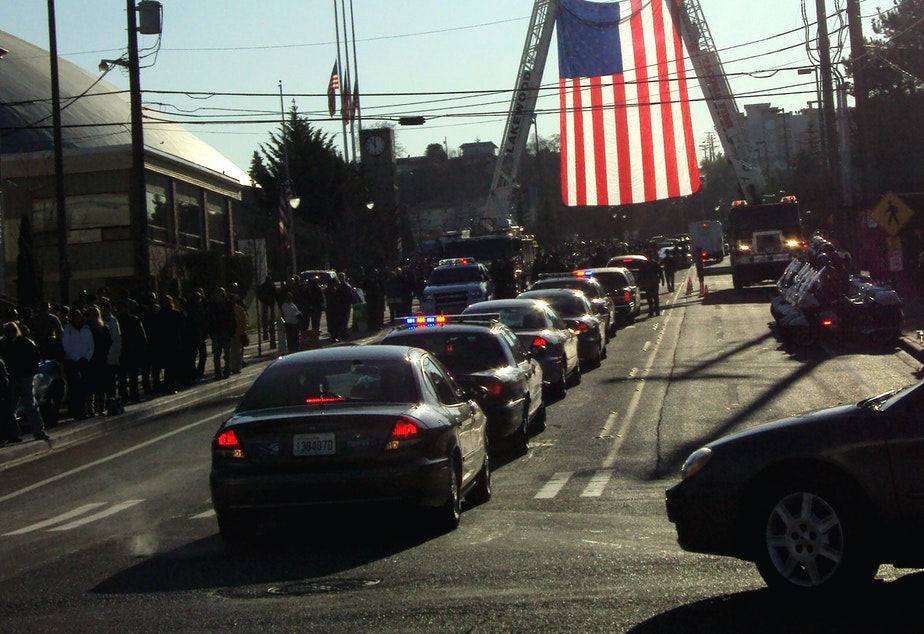 Police cars proceed through Tacoma during a memorial on Dec. 8, 2009 to four Lakewood officers who were shot to death.