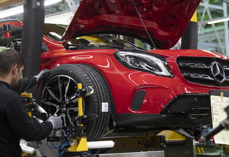An employee mounts a wheel on a Mercedes Benz A Class on the assembly line at the Daimler AG factory in Rastatt, southwestern Germany.
